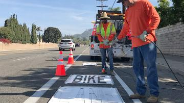 "Workers painting ""Bike Lane"" on a road"